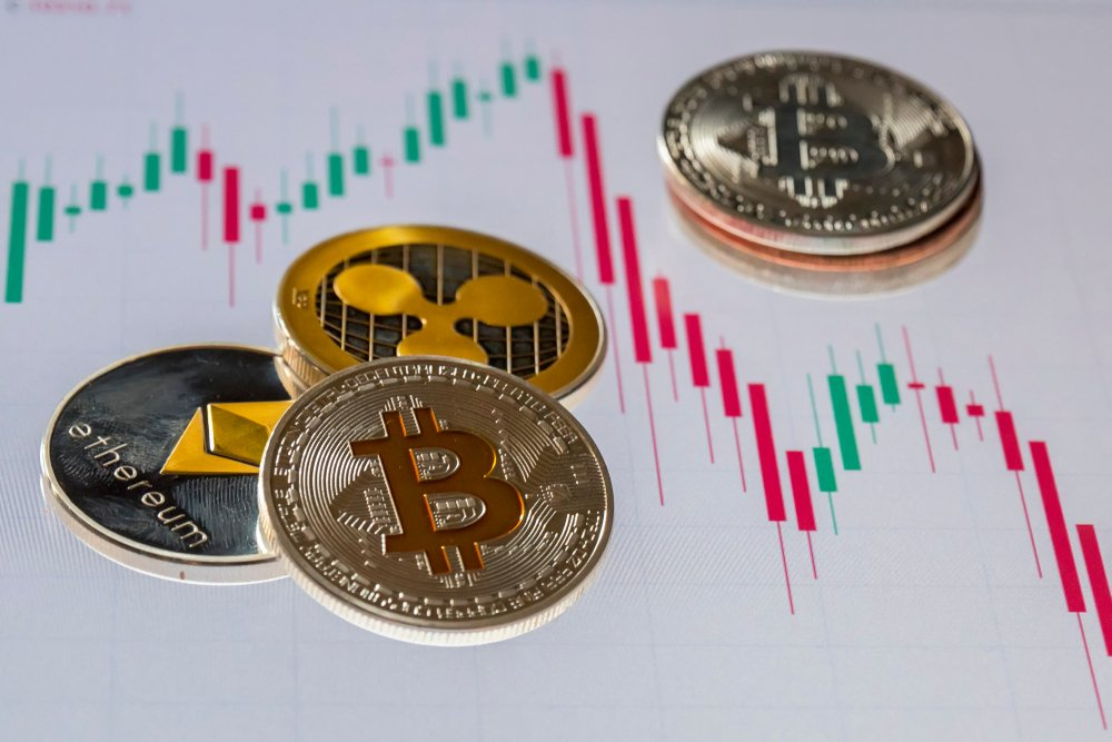 Cryptocurrency coins over trading candles graphic screen