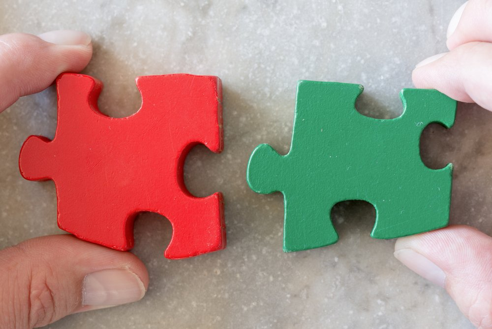 Two jigsaw pieces as metaphor for strong partnership