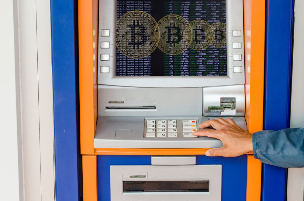 Woman holding a bitcoin on a ATM background