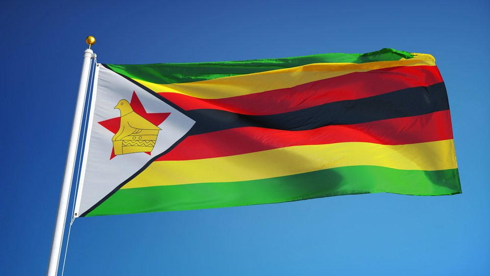 Zimbabwe flag waving against clean blue sky