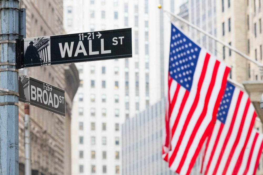Wall street sign in New York with American flags