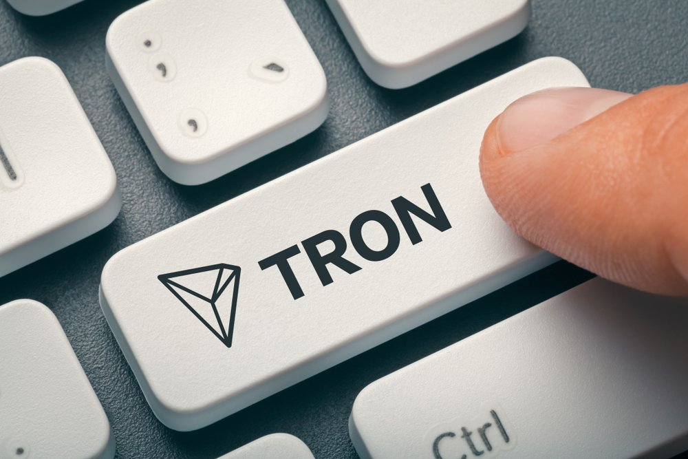 finger pressing computer key with tron coin logo