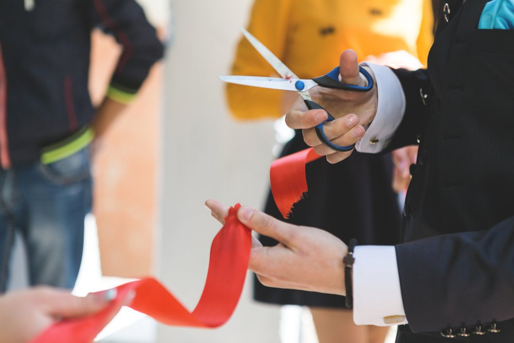 man cutting a red opening ceremony ribbok