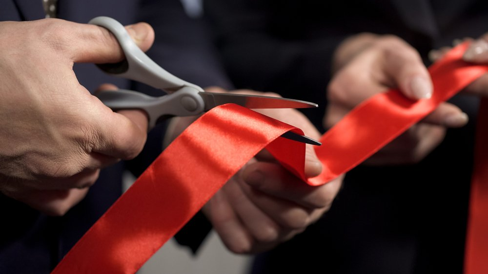 business people cutting a ribbon